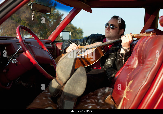 A rockabilly guy playing an acoustic guitar while sitting in his vintage car - Stock Image