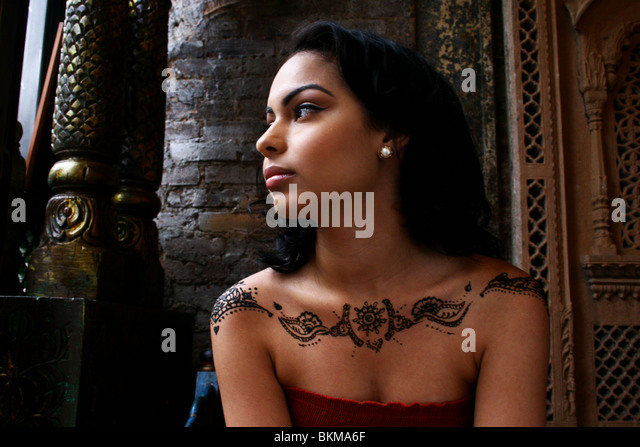 Portrait of woman painted with modern henna design on her shoulders. - Stock Image
