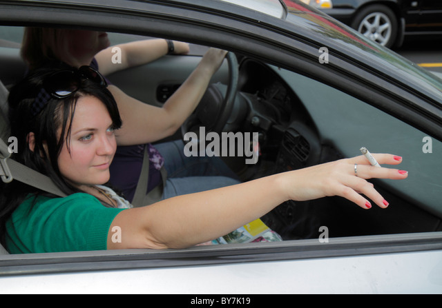 Nashville Tennessee car cruising girl teen student smoking holding lit cigarette habit addiction tobacco industry - Stock Image
