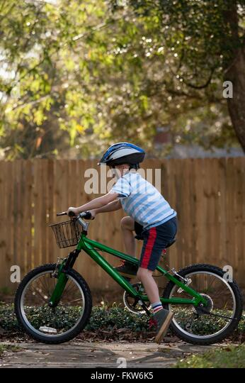 Boy riding bicycle past wooden fence - Stock-Bilder