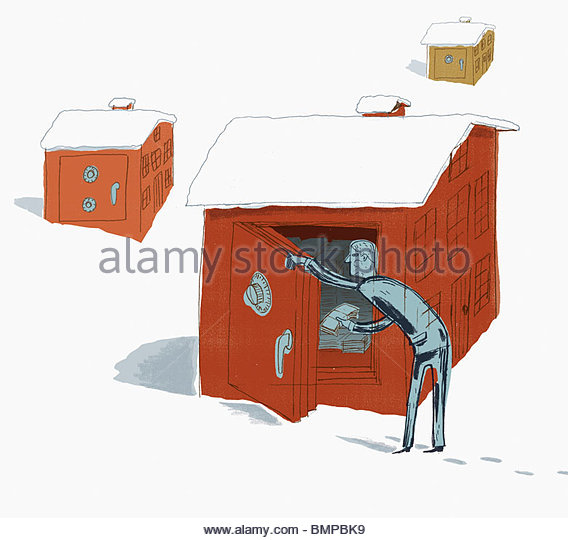 Man depositing money into snow covered safe - Stock Image