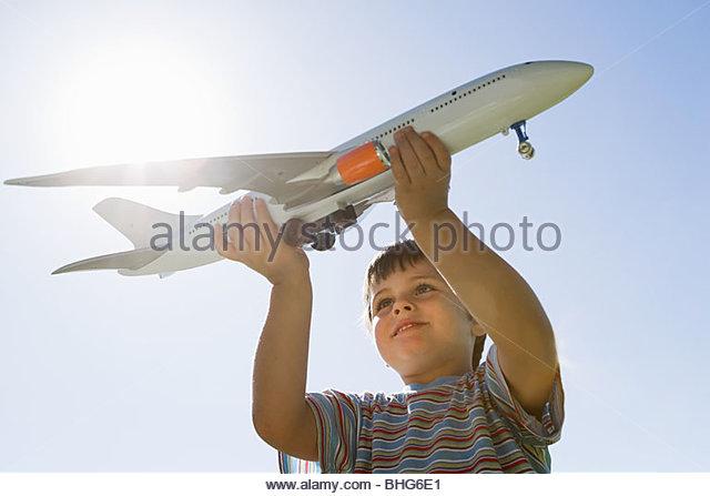 Little boy holding toy plane - Stock Image
