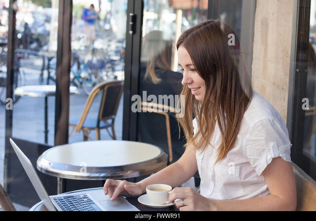 smiling young woman with computer in cafe - Stock-Bilder