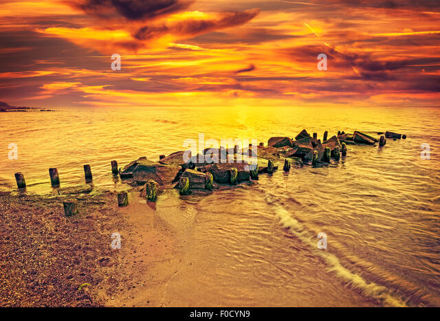 Vintage toned dramatic sunset over beach and rocky pier. - Stock Image