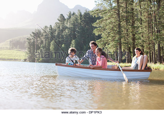 Family fishing in boat on lake - Stock Image