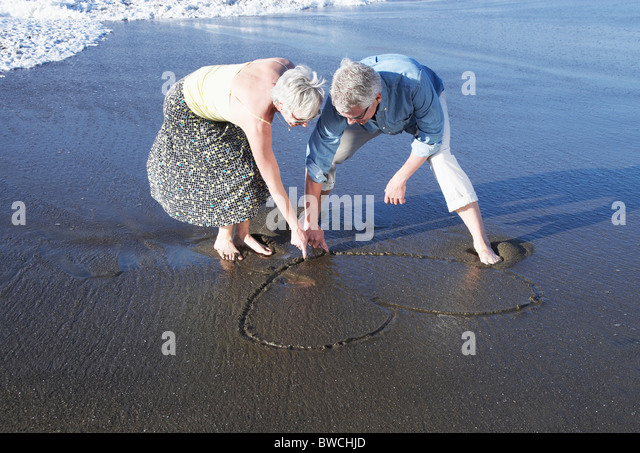 USA, California, Fairfax, Happy mature couple drawing heart on beach - Stock Image