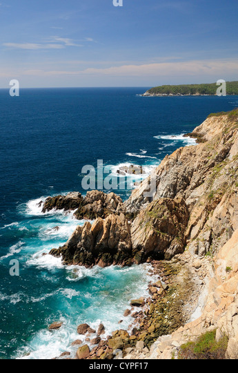 Mexico, Oaxaca, Huatulco, Rocky cliff edge with waves breaking on rocks below and Bahia Maguey on the Pacific coast. - Stock Image