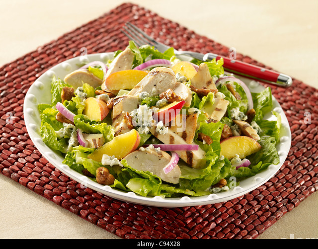 Fresh peach and chicken salad with onions, walnuts and crumbled cheese - Stock Image