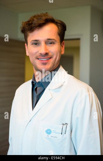 Portrait of male doctor smiling - Stock Image