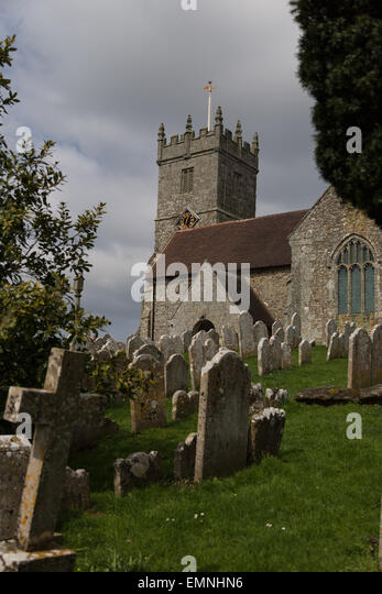 Moss-covered gravestones in front of the old church at Godshill, the Isle of Wight - Stock Image