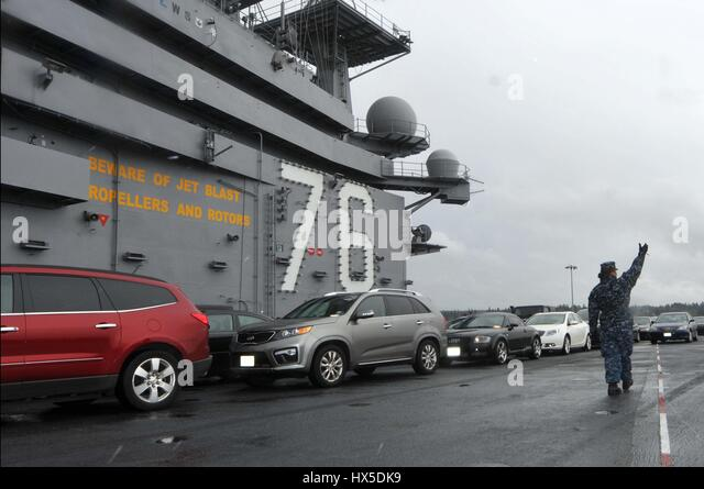 Carrying sailors' cars, aircraft carrier USS Ronald Reagan (CVN 76) departs from Bremerton, Washington for San - Stock Image