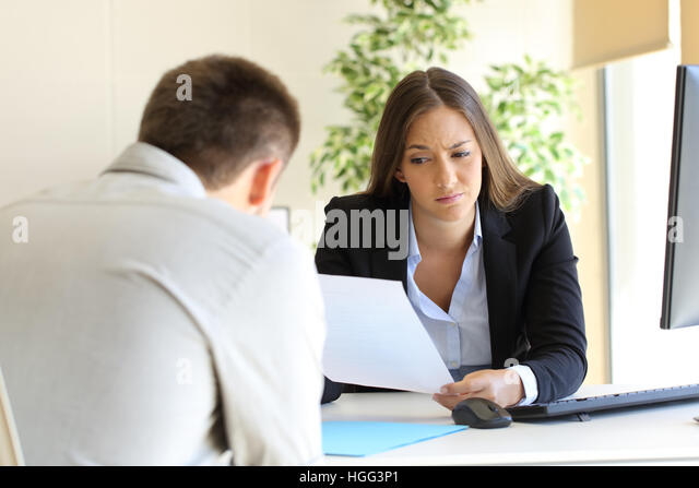 Businesswoman reading a bad resume in a job interview - Stock Image
