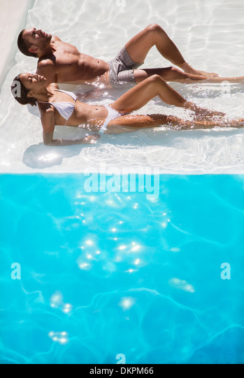 Couple sunbathing in swimming pool - Stock Image