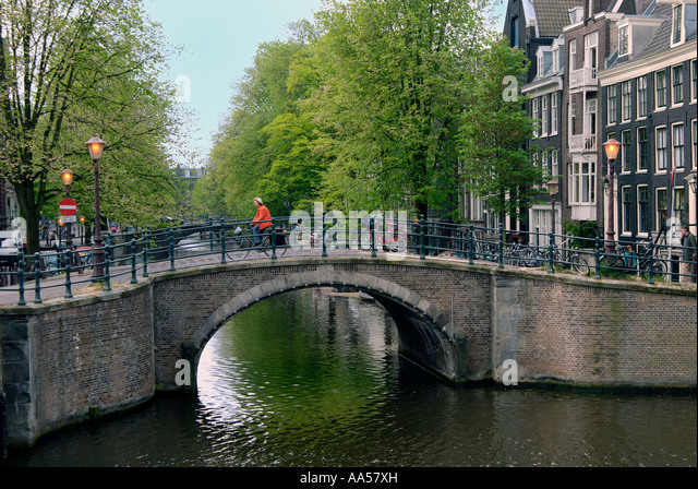 A blonde woman on a bike crossing a canal stone bridge in Amsterdam. Stock Photo