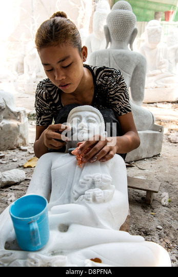 Burmese young woman crafting marble effigy of Buddha statue in the marble workshop district of Mandalay Burma Myanmar - Stock-Bilder