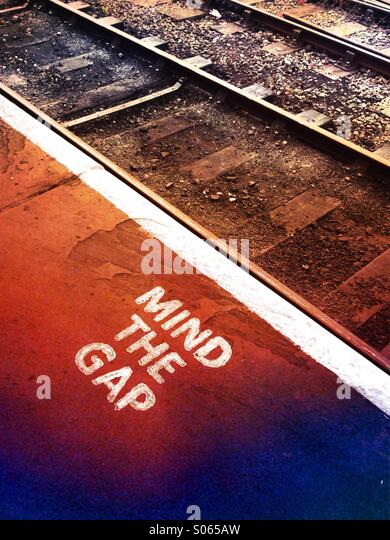 A mind the gap instruction at a railway - Stock Image