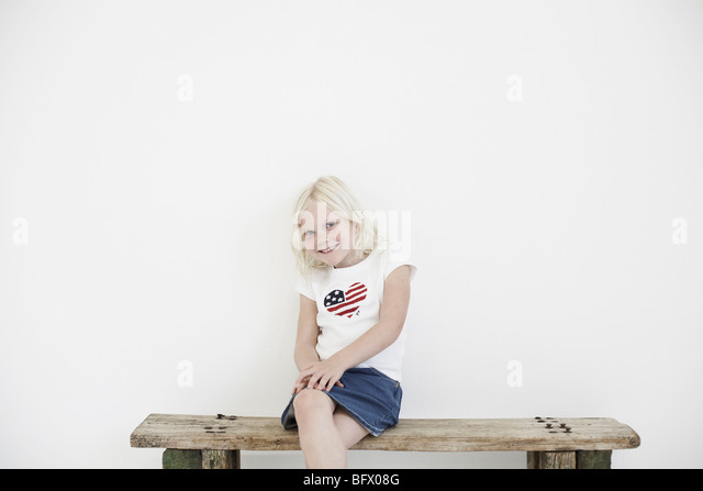 Girl on bench smiling to camera - Stock Image