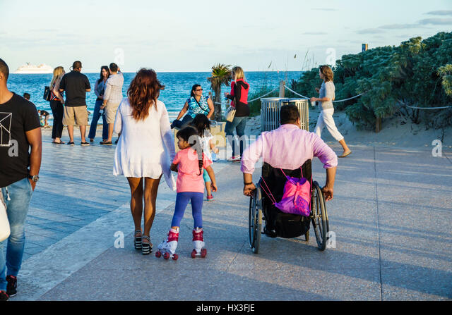 Miami Beach Florida Atlantic Ocean South Pointe Park woman father mother girl family wheelchair disabled man roller - Stock Image