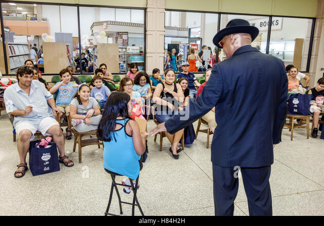 Miami Florida Hialeah JFK Library Health and Literacy Fair interior Black man magician show audience Hispanic girl - Stock Image