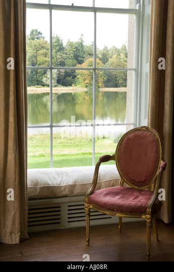 Louis XVI chair in front of a window with seat in 17th century Irish castle - Stock-Bilder