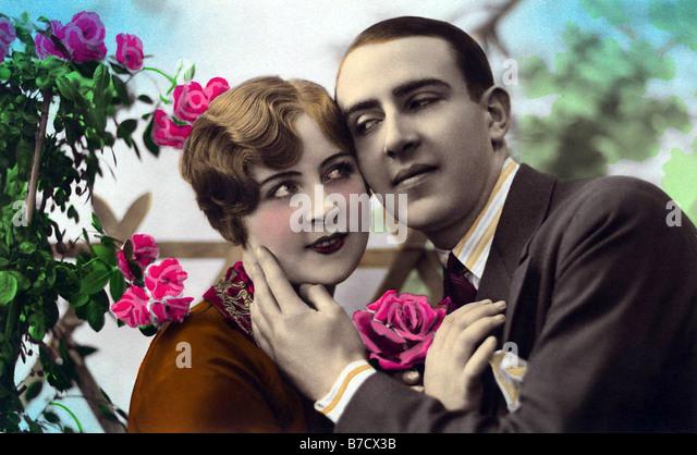 Tender embrace in summer with roses - Stock-Bilder
