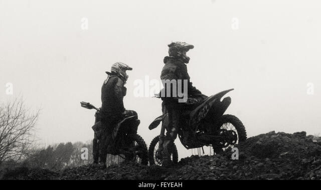 Low Angle View Of Men Sitting On Motorcycle Against Clear Sky - Stock Image
