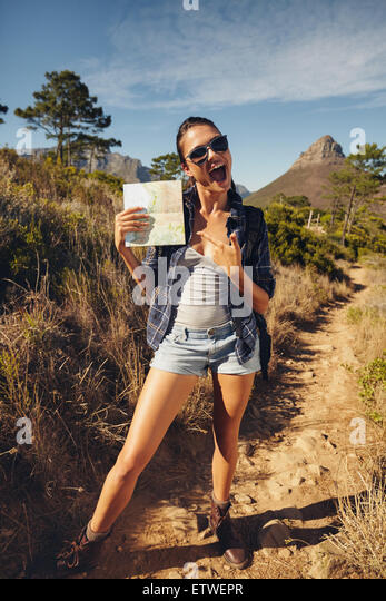 Portrait of excited young woman hiker showing a map. Caucasian woman hiking in countryside on summer day. - Stock Image