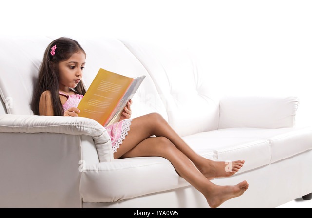 Little girl reading a story book - Stock Image