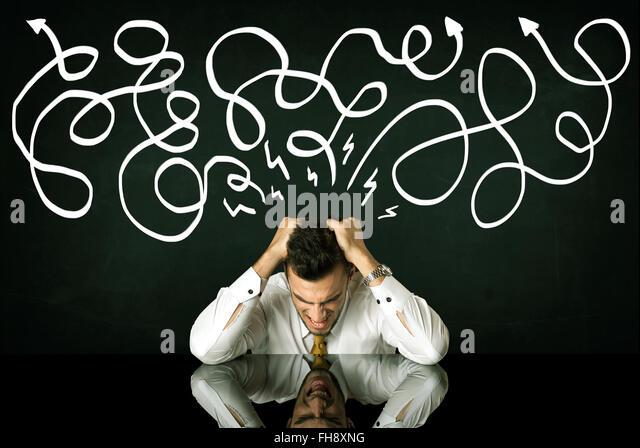 Depressed businessman sitting under drawn direction lines - Stock Image