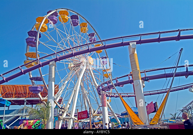 Looking up at Ferris wheel seats, roller coaster, rides on the Santa Monica pier California CA - Stock Image