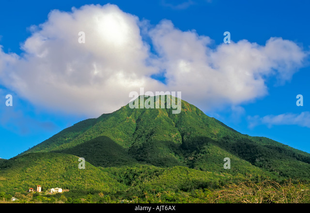 Mount Nevis Peak, symbol of the Caribbean island of Nevis, bright green forest, blue sky background, clear day - Stock Image