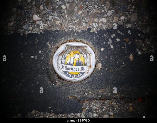 Soft drink metal caps stuck in road Asphalt - Stock Image