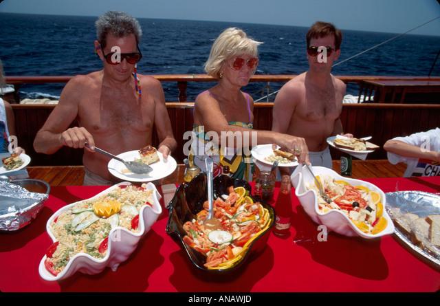 Venezuela Caribbean Sea Barefoot Windjammer SV Fantome passengers breakfast buffet schooner cruise men woman - Stock Image