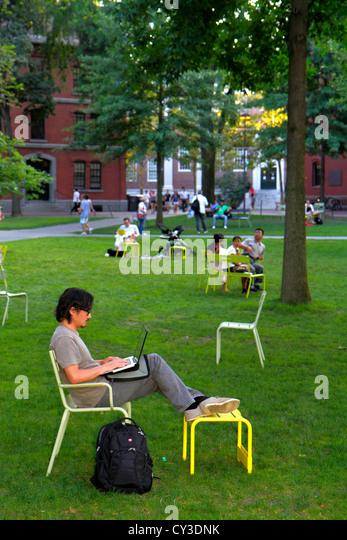 Boston Massachusetts Cambridge Harvard University campus Harvard Yard man student chairs sitting laptop computer - Stock Image