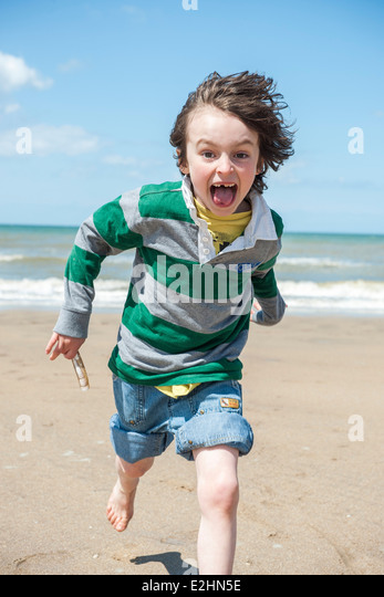 Boy playing at the beach - Stock Image