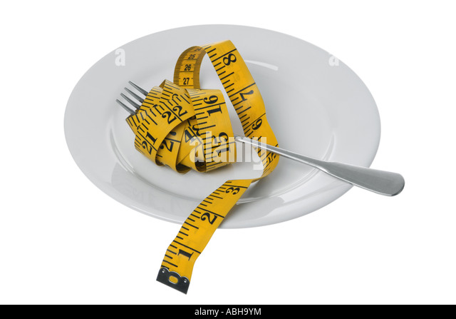 Tape measure with fork on plate cut out on white background - Stock Image