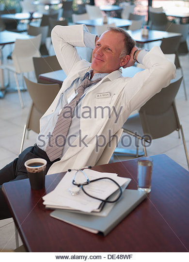 Doctor relaxing in cafeteria - Stock Image