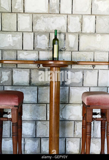 Wine bottle and wine glasses on a table with two bar stools - Stock Image