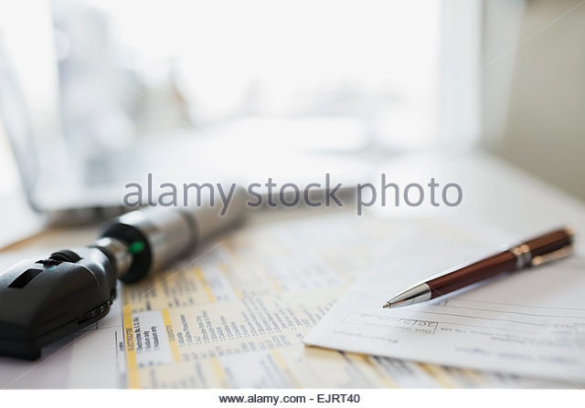 Otoscope, prescription and paperwork on doctors desk - Stock Image