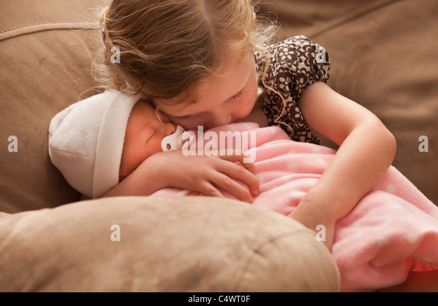 USA,Utah,Lehi,Girl (2-3) embracing baby sister on sofa - Stock Image