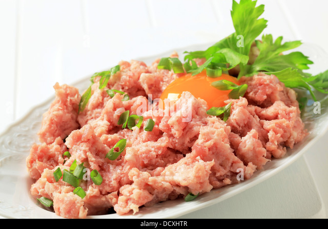 Fresh ground meat and egg yolk in a bowl - Stock Image