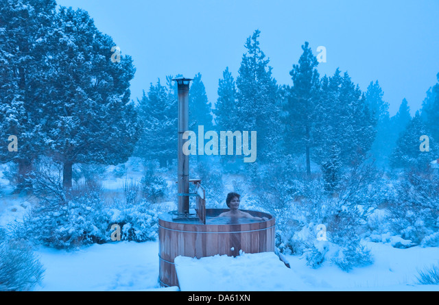 Woman, wood fired, hot tub, snow, winter, snowing, Central Oregon, USA, United States, America, Oregon, relax, wellness - Stock Image