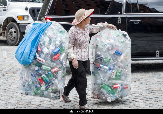 Lower Manhattan New York City NYC NY Tribeca cobblestone street Asian woman mature recycling aluminum cans bottles - Stock Image