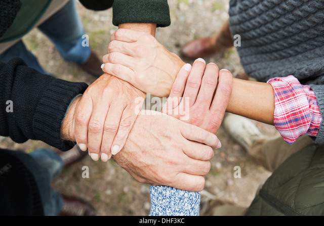 Four people touching hands, high angle - Stock Image