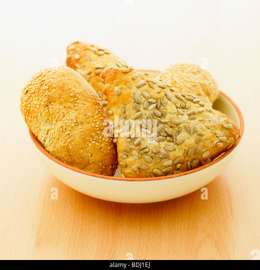 A selection of fresh rustic wholemeal bread rolls in a bowl. - Stock Image