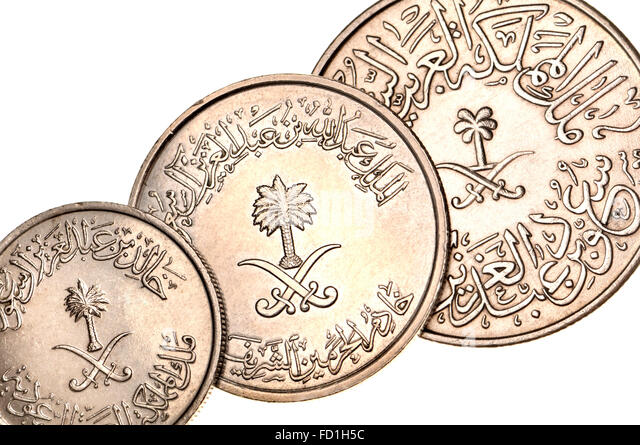 Coins of Saudi Arabia showing Eastern Arabic writing and numerals, palm tree and crossed swords - Stock Image