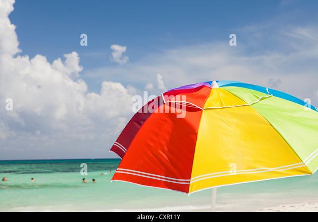 Bright beach umbrella on Playa Del Carmen, Quintana Roo, Mexico - Stock Image