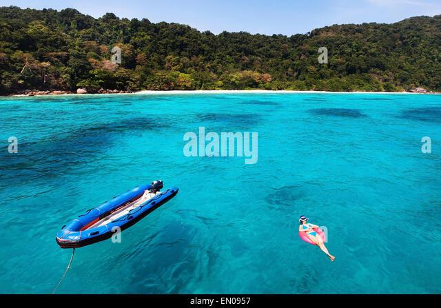 woman in bikini relaxing on turquoise beach, top view - Stock Image