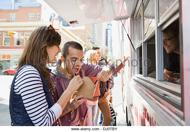 Couple eating meal from a food truck - Stock Image