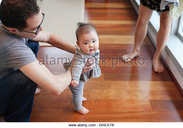 Father helping baby girl to stand - Stock Image